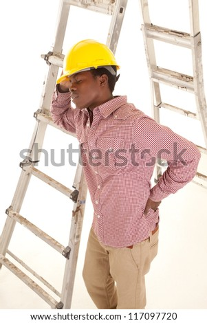 A construction worker taking a break by leaning up against the ladder.