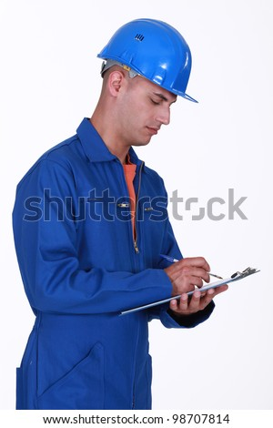 A construction worker taking notes. - stock photo