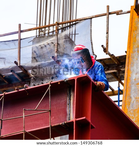 A Construction Worker welding steel bars on construction site. - stock photo