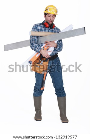 A construction worker with his arms loaded.