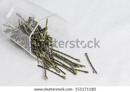 A container of bobby hair pins pouring out. - stock photo