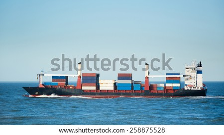 A container ship transports containers. Photographed at sea under a clear blue sky.