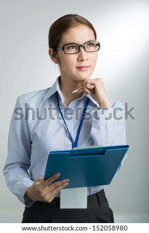 A contemplating businesswoman thinking over the strategy over a grey background - stock photo