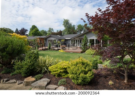 A contemporary home can be seen beyond the backyard lawn with rock and evergreen landscaping in the foreground on a mild summer day in the Pacific Northwest. - stock photo