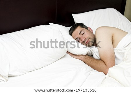 A content man sleeping in bed on crisp white sheets.