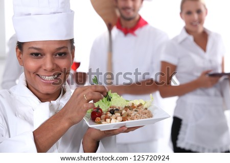 a cook holding a dish, a pizza cook and a waitress dressed in uniform - stock photo