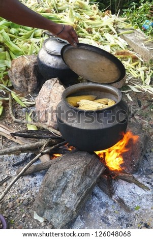A cook pot with Indian corn on a fire place - stock photo
