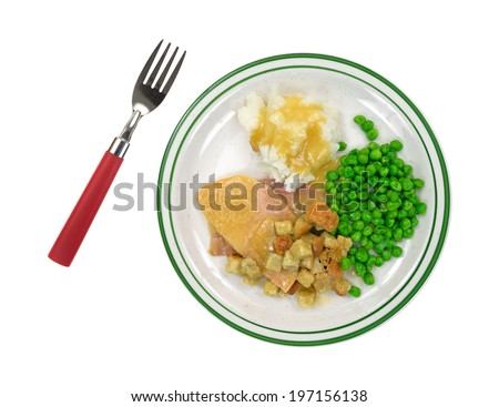 A cooked sliced turkey in gravy with croutons, mashed potatoes and green peas on a plate with red handled fork to the side. - stock photo