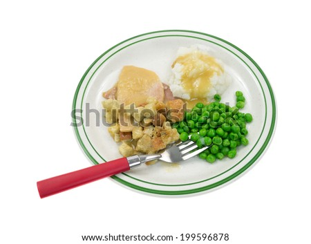 A cooked sliced turkey in gravy with croutons, mashed potatoes and green peas on a plate with red handled fork on a white background. - stock photo