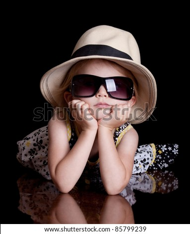 A cool image of a cute little girl wearing a hat and sunglasses. - stock photo