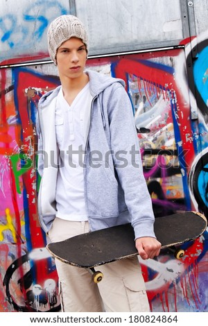 a cool-looking teenager man in front of graffiti - stock photo