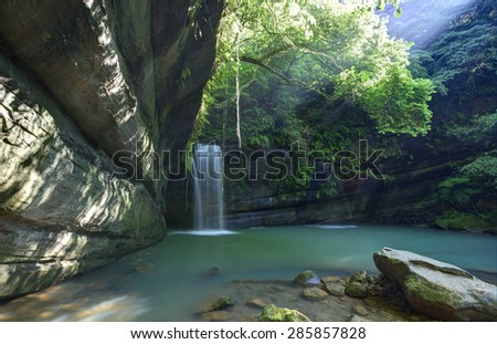 A cool refreshing waterfall pouring into a green pond in a mysterious forest of lush greenery with sunlight leakage ~ Scenery of Taiwan - stock photo