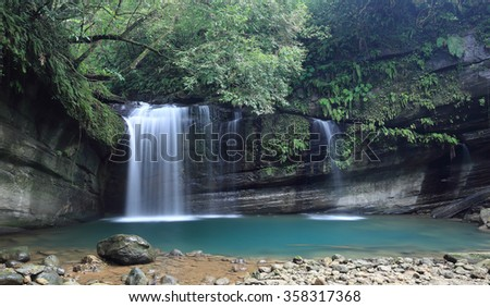 A cool refreshing waterfall pouring into an emerald pond hidden in a mysterious forest of lush greenery ~ A scenic paradise with beautiful waterfall and intriguing river potholes in Taiwan - stock photo