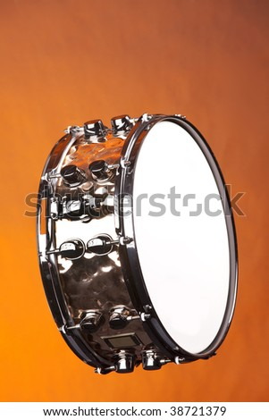 A copper snare drum isolated against a yellow or gold background in the vertical format.