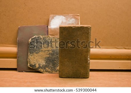 A cork sanding block. This is in front of various grades or grits of sandpaper and a length of decorative timber.