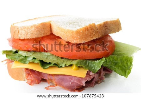 A corned beef sandwich with lettuce tomatoes and cheese.