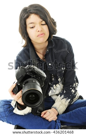 A corner image of an attractive young teen unhappy with the image in the back of her pro camera.  On a white background.   - stock photo