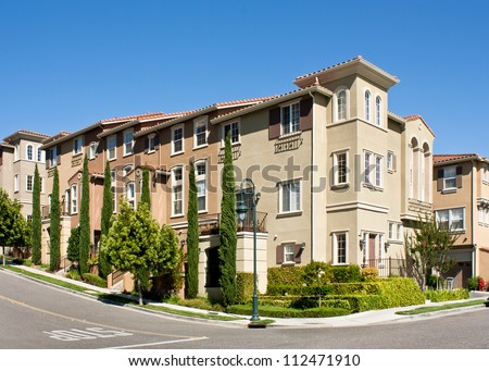 A corner view of a new multi-story townhome development in California. - stock photo