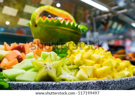 A cornucopia of fruit with a carved watermelon basket