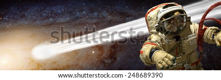 A cosmonaut floats in deep space while tethered to his ship. A massive comet passes near him on its way towards the sun it orbits.  Elements of this Image Furnished by NASA. - stock photo