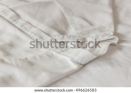 a cotton white pajamas(sleepwear, nightshirt, pj's, nightdress, nightie) with wood hanger closeup on the bed at the bedroom in hotel, seoul