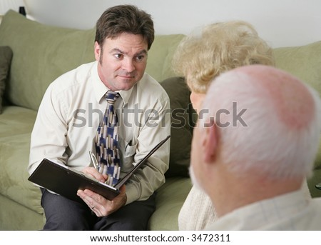 A counselor with a caring expression sitting across from an elderly couple.