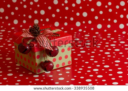 A country Christmas gift box with red polka dots and jingle bells topped with a pine cone on a red and white background