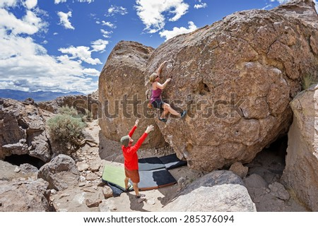 a couple bouldering at the Happy Boulders with the woman climbing and the man spotting - stock photo