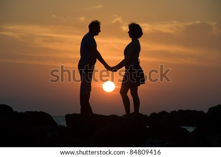 A couple by sunset on a pier looking to each other romantically