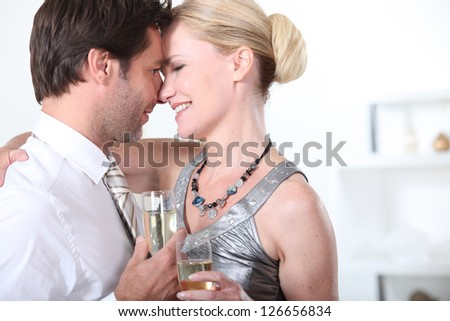 A couple celebrating with a glass of champagne - stock photo