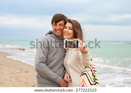 A couple doing selfie at the sea