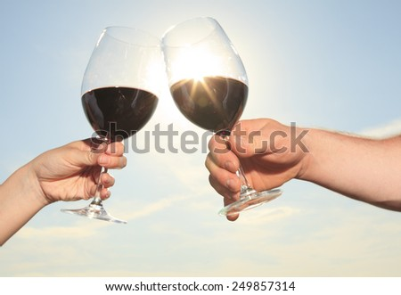 A couple drinking a bottle of red wine outside - stock photo