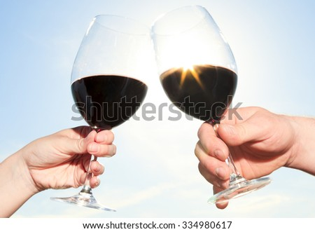 A couple drinking a bottle of red wine outside