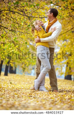 A couple embracing and laughing among autumn trees