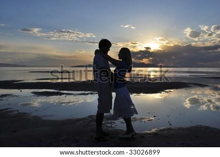 A couple embracing near a lake at sunset - stock photo