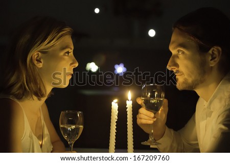 A couple engage in a serious conversation over a glass of white wine in candlelight. - stock photo