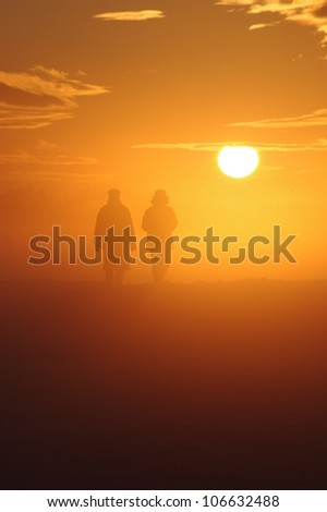 a couple have a walk through a misty landscape