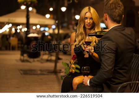 A couple having an elegant toast with red wine at night - stock photo