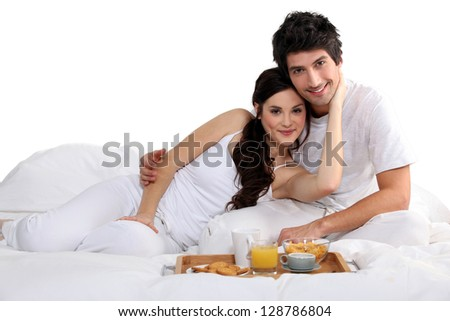 a couple having breakfast on bed - stock photo