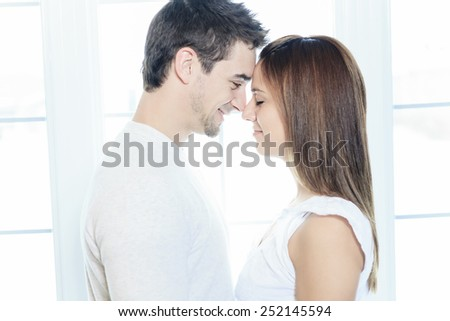 A couple having great time close to the window - stock photo