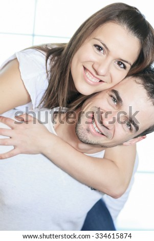 A couple having great time close to the window on piggyback. - stock photo