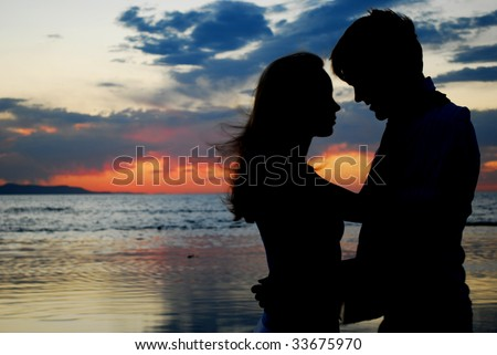 A couple holding each other during a brilliant sunset - stock photo