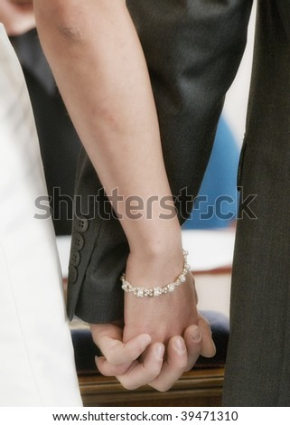 A couple holding hands as they get married