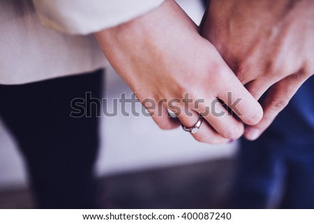 A couple holding hands. Closeup - stock photo