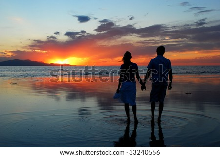 A couple holding hands during an amazing sunset - stock photo