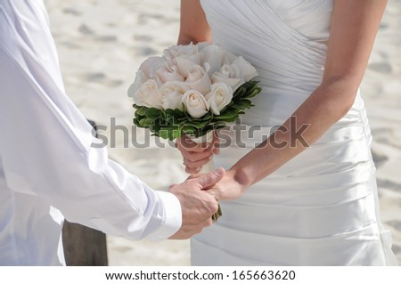 A couple holding their hands at wedding ceremony - stock photo