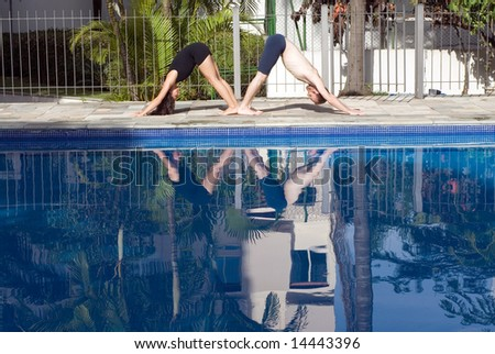 A couple, in a v-shape stretch position, stretch by the poolside - horizontally framed