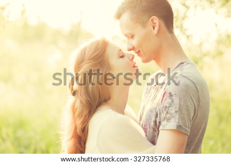 A couple in love beautiful young men kissing in a summer park on a sunny day - stock photo