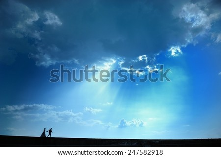 A couple in love in dramatic blue sky. Peaceful romantic moment.  - stock photo