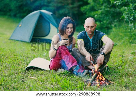 a couple in love is sitting at the fire
